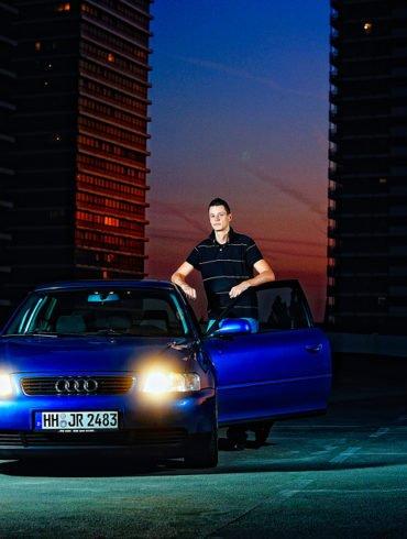 Besitzer und Auto bei Sonnenuntergang