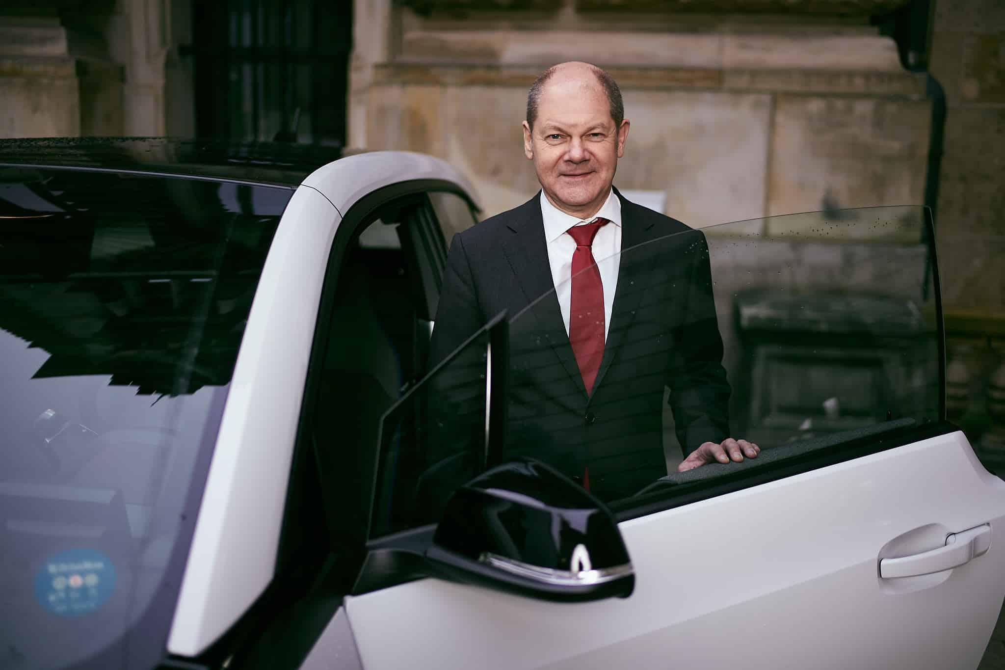 Olaf Scholz vor dem e-Auto von drive now